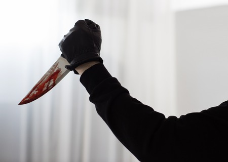 hand in glove with blood on knife Stock Photo