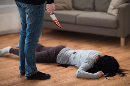 criminal with knife and dead body at crime scene Stock Photo