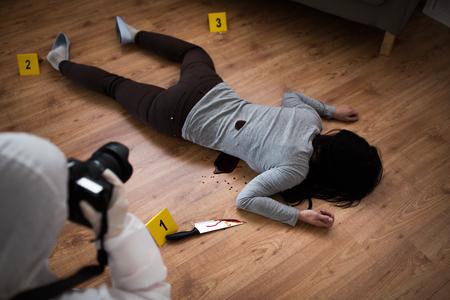 criminalist photographing dead body at crime scene
