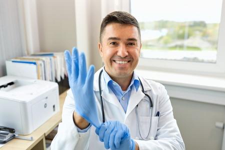 クリニックで保護手袋を持つ笑顔の医師
