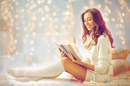 happy young woman reading book in bed at home Фото со стока - 90575493
