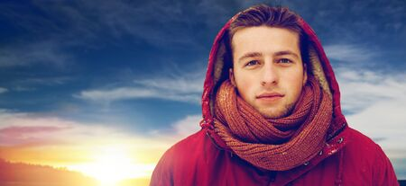 happy man in winter jacket with hood outdoors Stock Photo