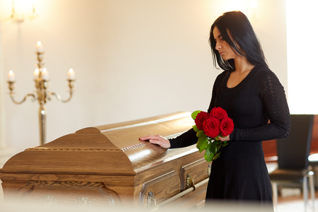 sad woman with red rose and coffin at funeral