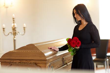 trieste vrouw met rode roos en doodskist bij de begrafenis