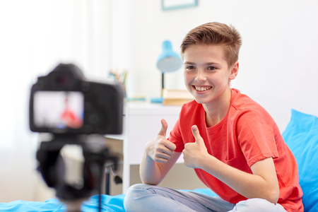 happy boy with camera recording video at home Stockfoto