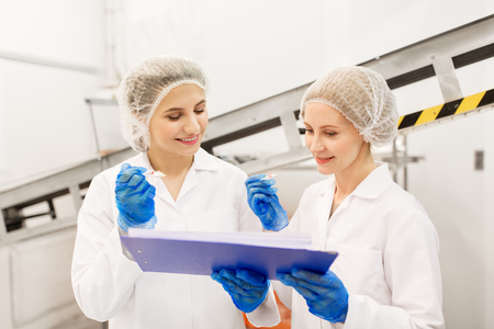 women technologists tasting ice cream at factory Zdjęcie Seryjne - 90575562
