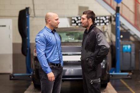 auto mechanic talking to customer at car shop