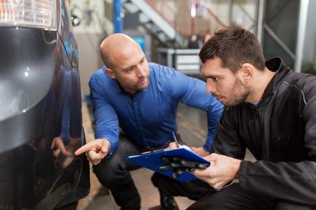 自動車整備士と車を見ている顧客
