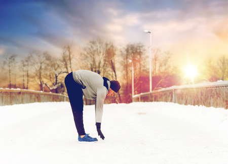 man exercising and stretching leg on winter bridge
