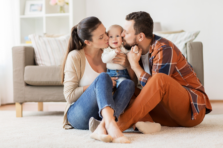 happy mother and father kissing baby at home Standard-Bild