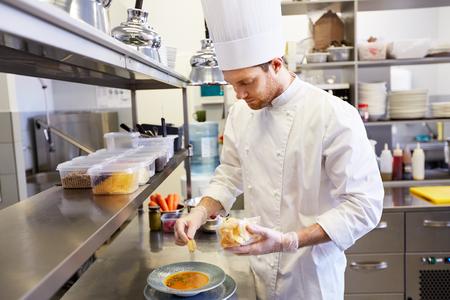 Cuoco unico maschio felice che cucina alimento alla cucina del ristorante Archivio Fotografico - 90769408