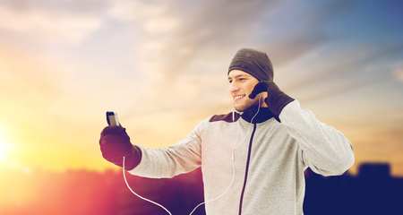 happy man with earphones and smartphone in winter Stock Photo