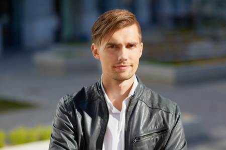 portrait of young man in leather jacket outdoors