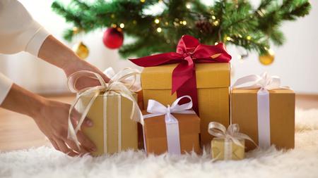 handen zetten geschenkdozen onder de kerstboom Stockfoto