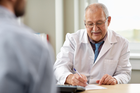 doctor writing prescription for patient at clinic Stock Photo