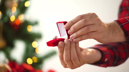 close up of hands with ring in christmas gift box