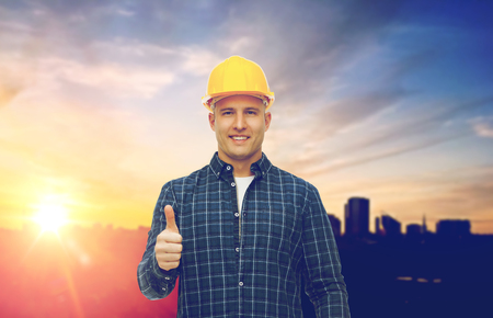 mannelijke bouwer in gele helm tonen duimen omhoog