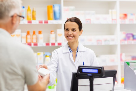 apothecary selling drug to senior man at pharmacy Stock Photo - 90840711