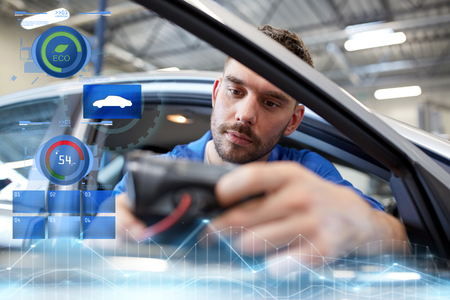 mechanic man with diagnostic scanner at car shop 版權商用圖片
