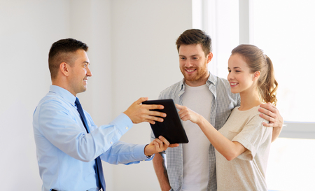 couple and realtor with tablet pc at new home Stock Photo