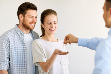 realtor giving keys from new home to happy couple