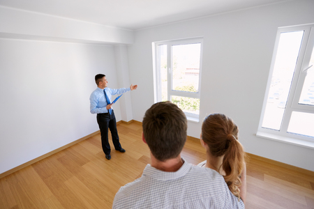 realtor with clipboard and couple at new home