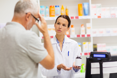 apothecary showing drug to senior man at pharmacy Фото со стока