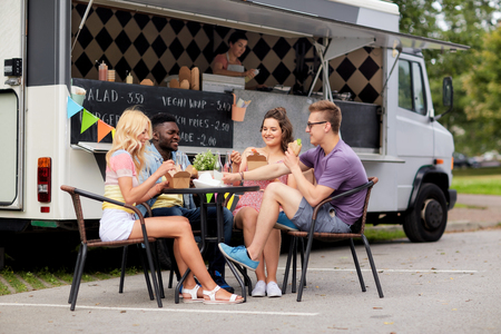 happy friends with drinks eating at food truck Stock fotó