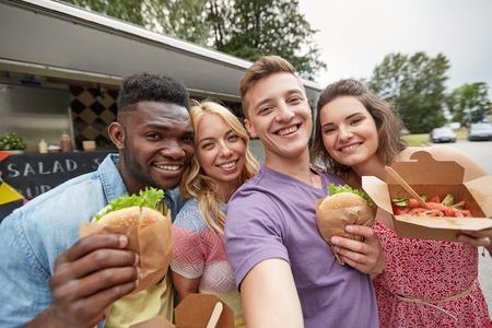 happy friends taking selfie at food truck
