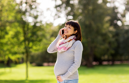 pregnant asian woman calling on smartphone at park