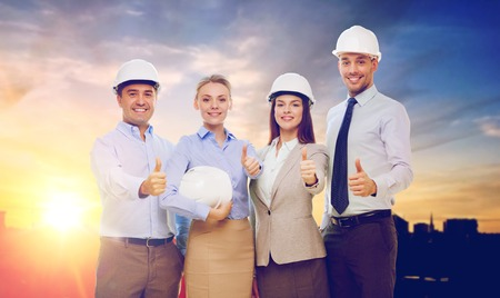 business team in white hard hats showing thumbs up Banco de Imagens