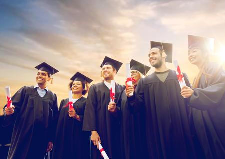 glückliche Studenten in Mörserbrettern mit Diplomen