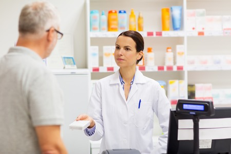 apothecary showing drug to senior man at pharmacy Stock Photo