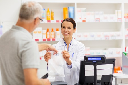 fabricante de drogas de ayuda a un hombre mayor en farmacia