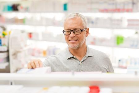 senior male customer with drug at pharmacy