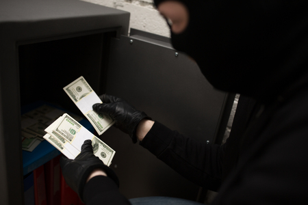 thief stealing money from safe at crime scene Stock Photo