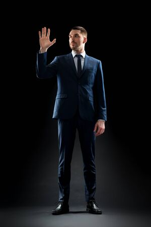 businessman in suit touching something invisible