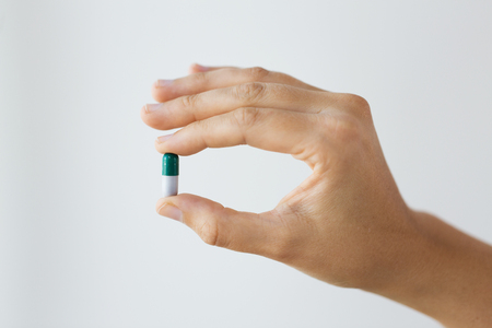 close up of hand holding capsule of medicine Stock Photo
