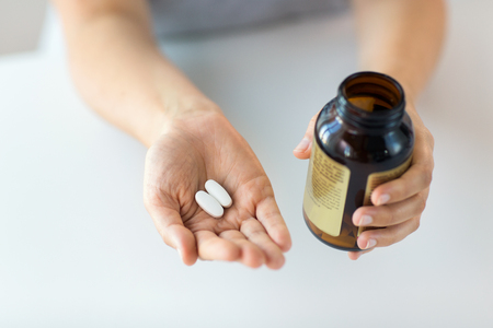 close up of hands holding medicine pills and jar