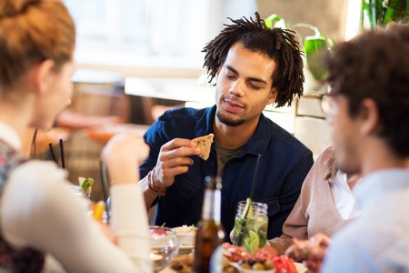 man with friends eating at restaurant