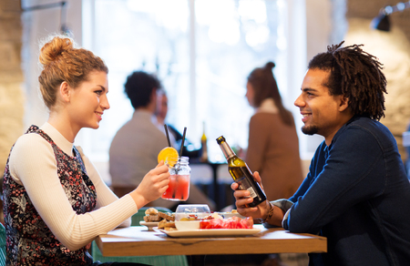 happy couple with drinks at restaurant or bar