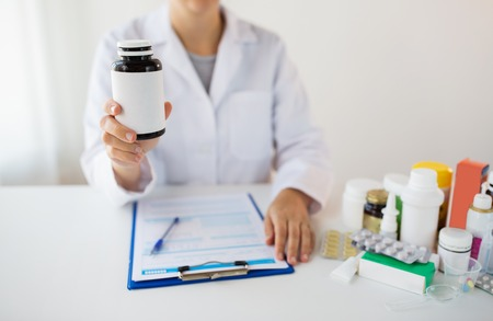 close up of doctor with medicines and clipboard