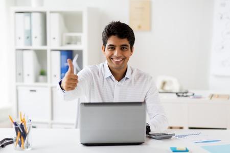 Geschäftsmann , der Daumen hoch im Büro zeigt