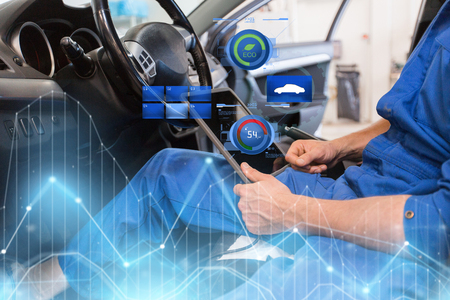 mechanic man with tablet pc making car diagnostic Фото со стока