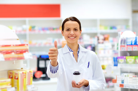 apothecary with drug showing thumbs up at pharmacy