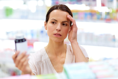 customer with headache choosing drugs at pharmacy