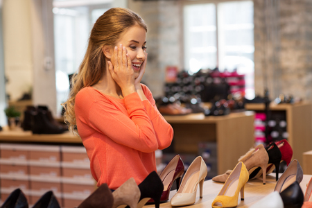 excited young woman choosing shoes at store Imagens