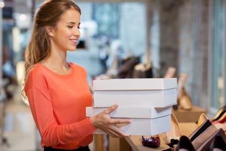 vrouw of winkelmedewerker met schoenendozen in winkel