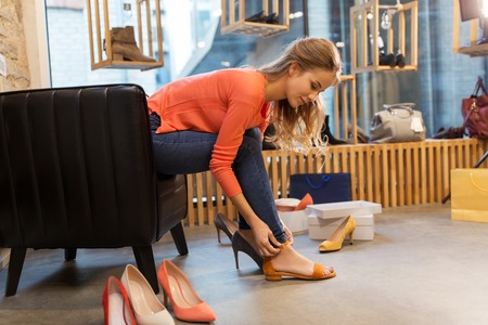young woman trying sandals at shoe store Standard-Bild