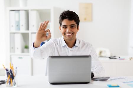 オフィスでOKサインを示すラップトップを持つビジネスマン 写真素材
